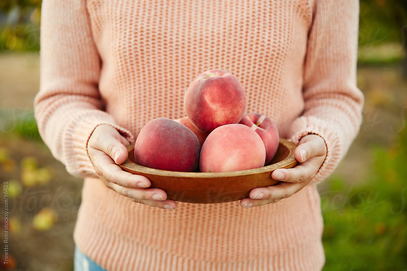 Woman holding bowl of peaches on farm by Trinette Reed for Stocksy United