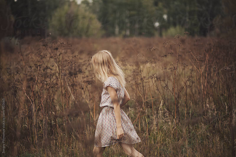 Girl goes across the field in a pink dress by Sergey Filimonov for Stocksy United