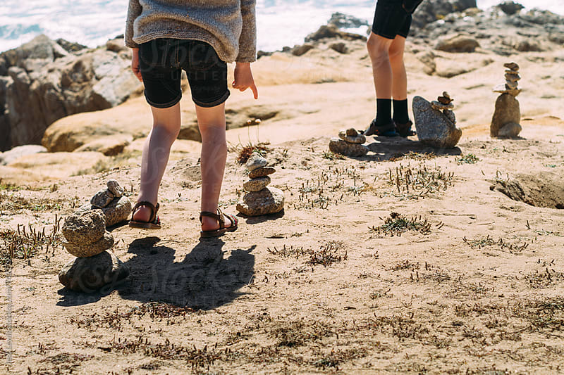 siblings standing next to cairns at the beach by Jess Lewis for Stocksy United