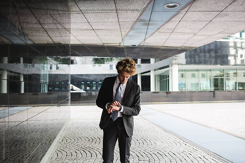 Young businessman checks the time by michela ravasio for Stocksy United