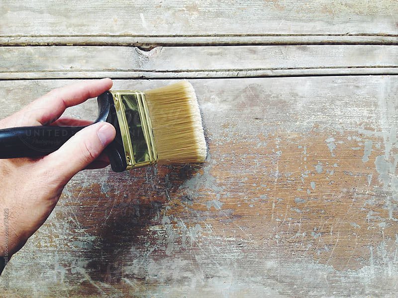 Paint brushes on a wooden board by Greg Schmigel for Stocksy United