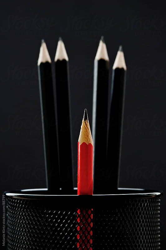 one smaller red pencile among a group of other black pencils before black background by Melanie Kintz for Stocksy United