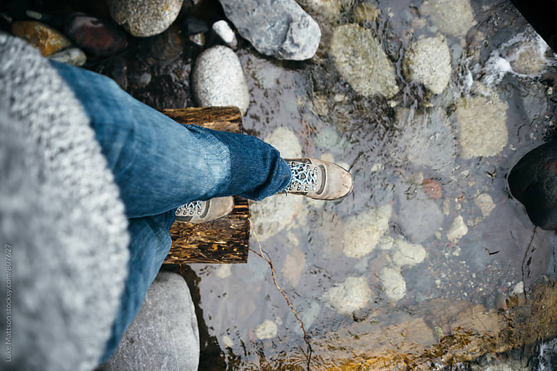 Man In Hiking Boots Balancing On Edge of Log Above River by Luke Mattson for Stocksy United