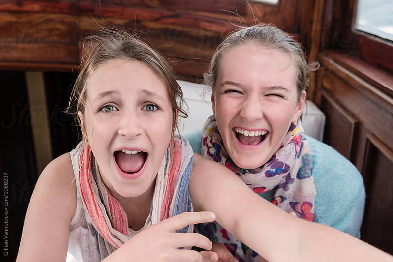 two teen girls laughing together by Gillian Vann for Stocksy United