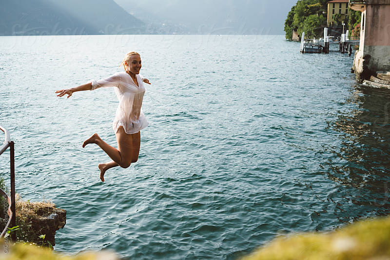 Happy woman diving in the lake by GIC for Stocksy United