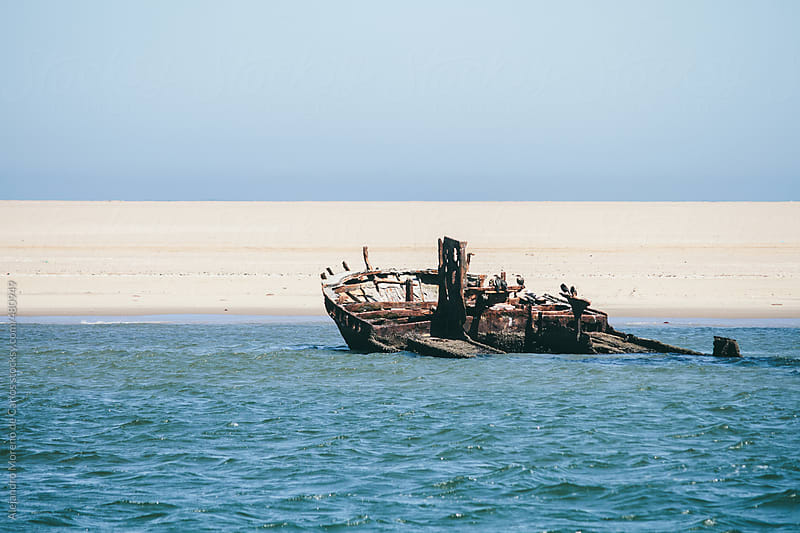 Rusty shipwreck on a deserted beach by Alejandro Moreno de Carlos for Stocksy United