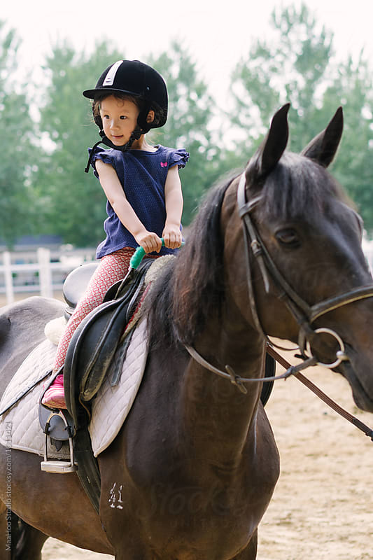 Cute little girl riding horse by Maa Hoo for Stocksy United