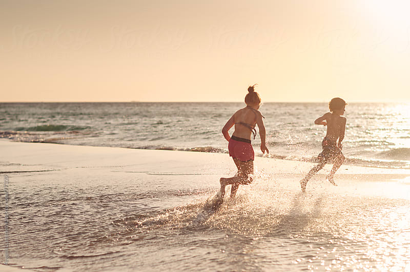 Children playing in water at the beach by Angela Lumsden for Stocksy United