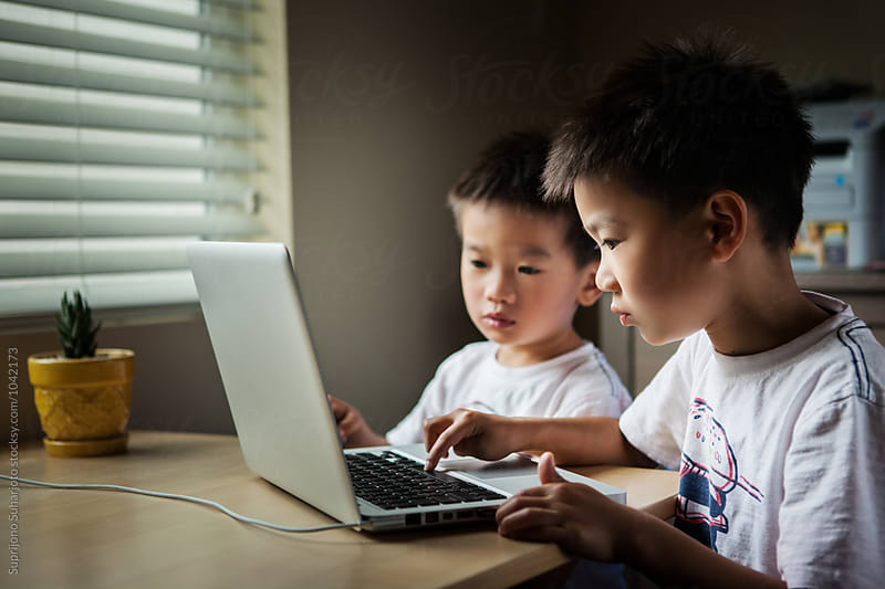Asian kids using a laptop at home by Suprijono Suharjoto for Stocksy United