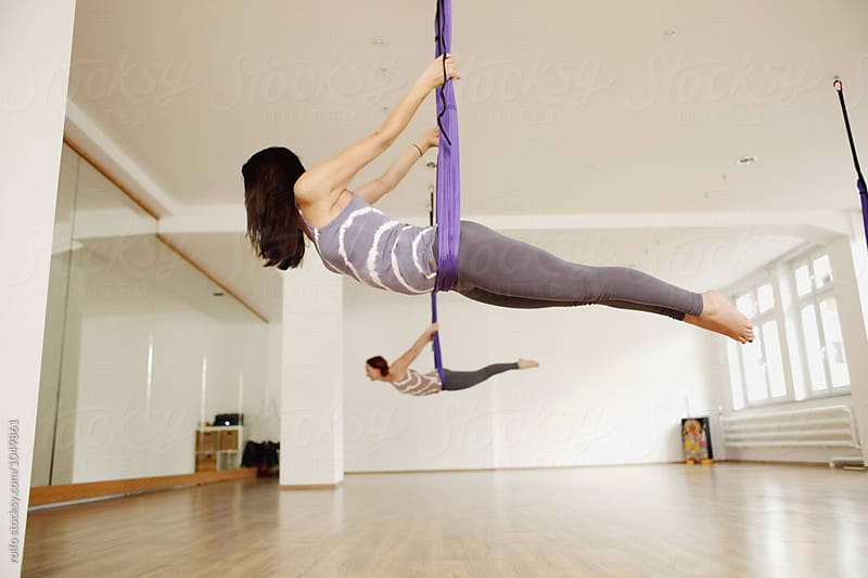 Two women doing aerial yoga exercise by rolfo for Stocksy United