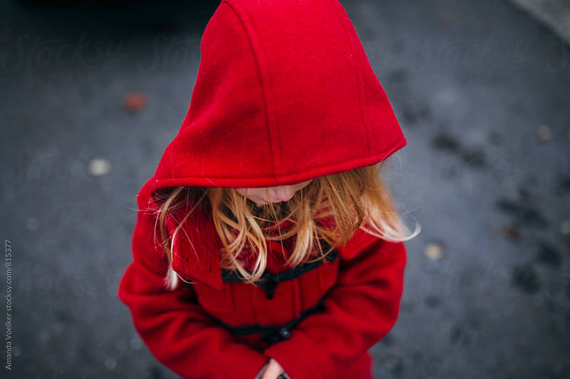 A Little Girl in A Hooded Red Coat with Her Face Mostly Hidden by Amanda Voelker for Stocksy United