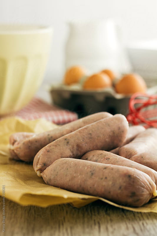 Linked sausages with cooking scene behind by Kirsty Begg for Stocksy United