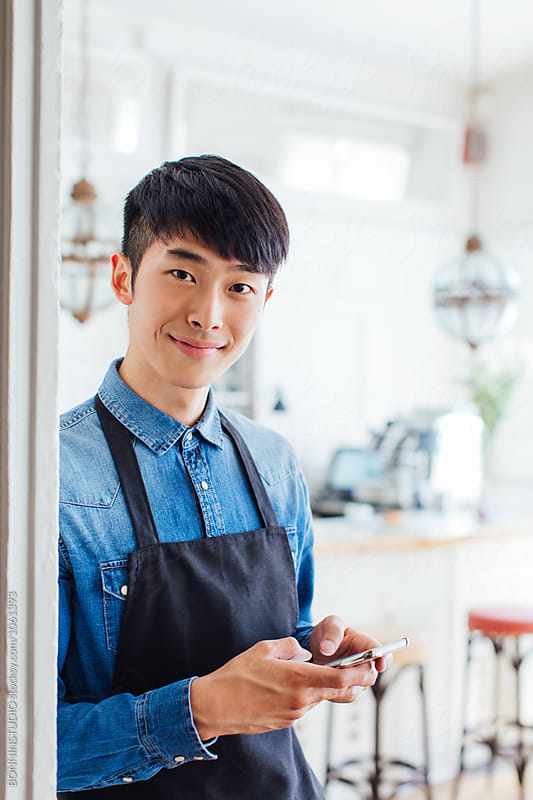 Young asian waiter using his phone in a restaurant.  by BONNINSTUDIO for Stocksy United