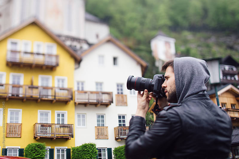 Bearded photographer taking photo of countryside village by Andrey Pavlov for Stocksy United
