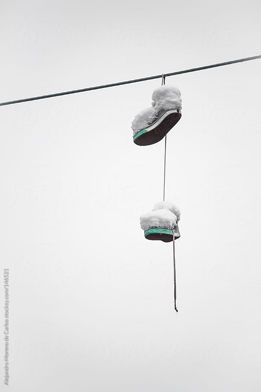 Shoes covered in snow hanging on electricity cable by Alejandro Moreno de Carlos for Stocksy United