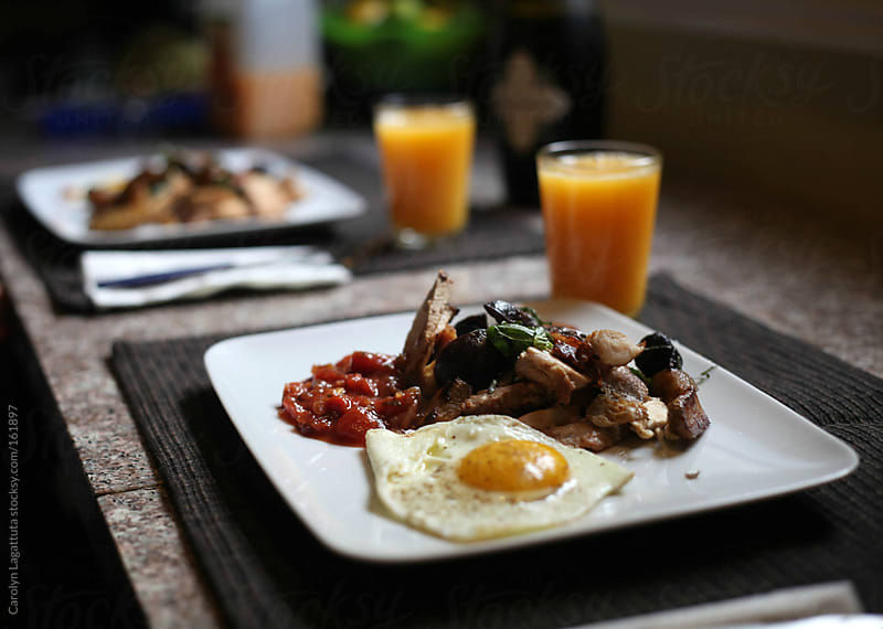 Hearty breakfast with sunny side up eggs, pork, potatoes and salsa by Carolyn Lagattuta for Stocksy United