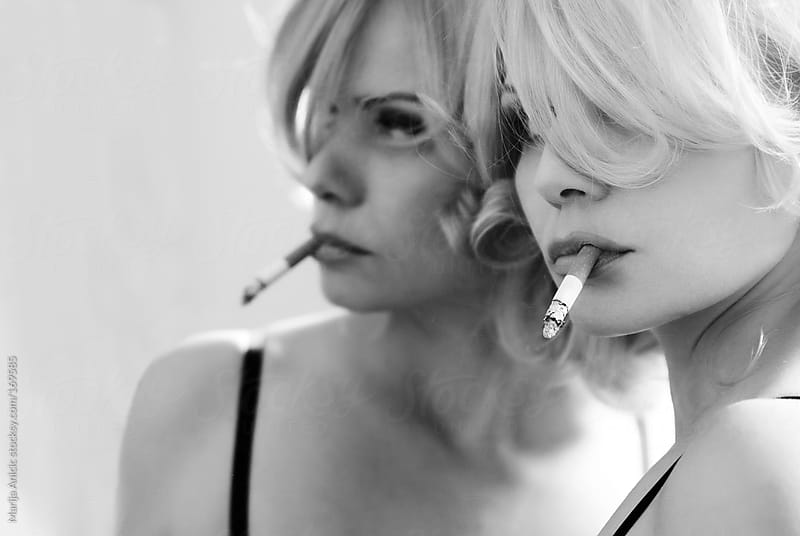 Blonde woman,mirror,phone,camera and cigarettes by Marija Anicic for Stocksy United