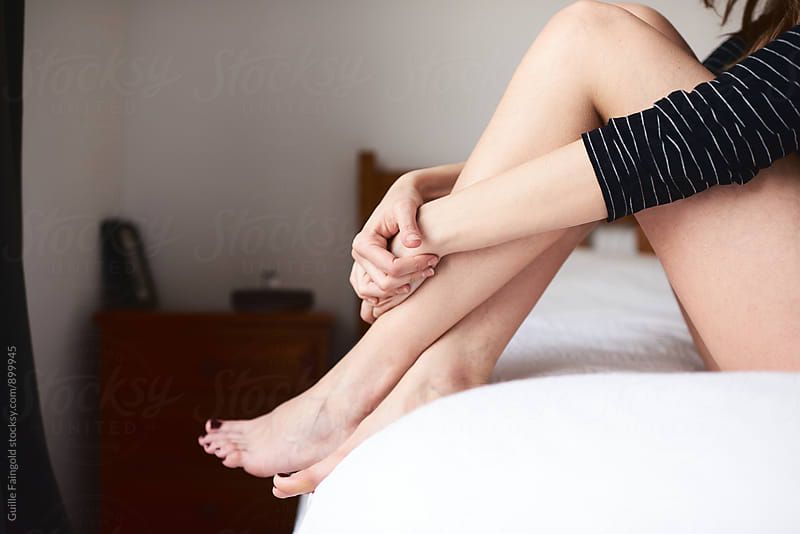 Woman embracing her legs while sitting on bed by Guille Faingold for Stocksy United