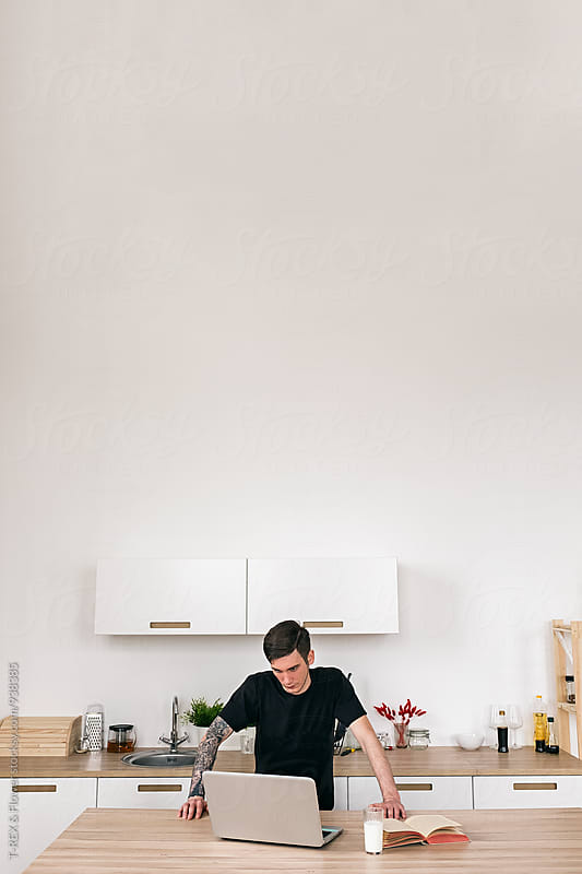 Man with laptop in kitchen by Danil Nevsky for Stocksy United