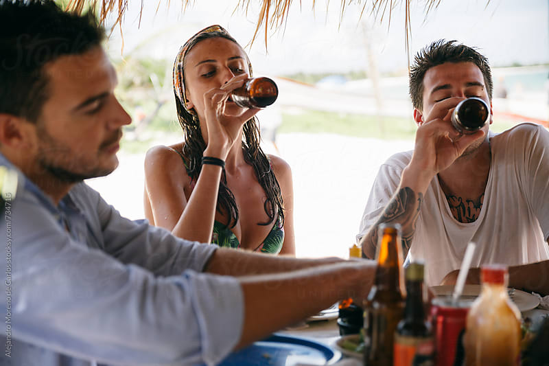Group of friends drinking beer and enjoying a meal in a beach restaurant by Alejandro Moreno de Carlos for Stocksy United