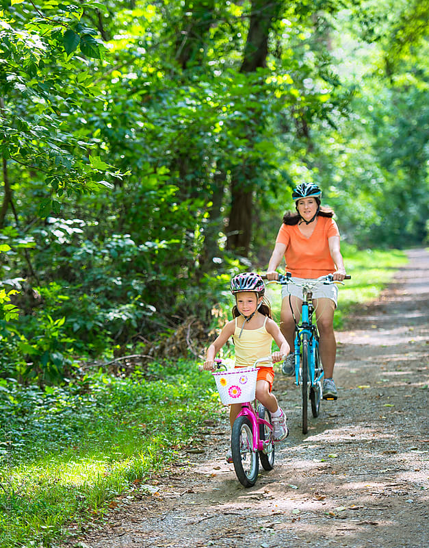 Family: Mother and Daughter Riding on Wooded Path by Brian McEntire for Stocksy United
