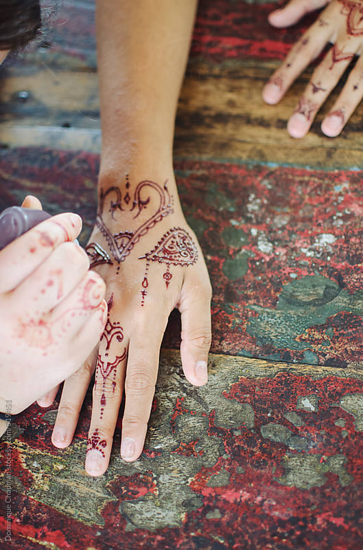 Henna tattoo being painted on hands by Dominique Chapman for Stocksy United