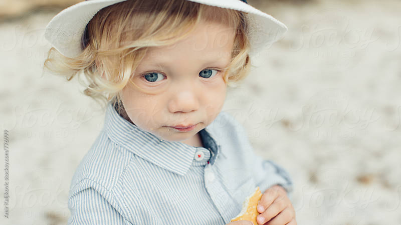 Cute little blond boy with a solemn expression by Amir Kaljikovic for Stocksy United