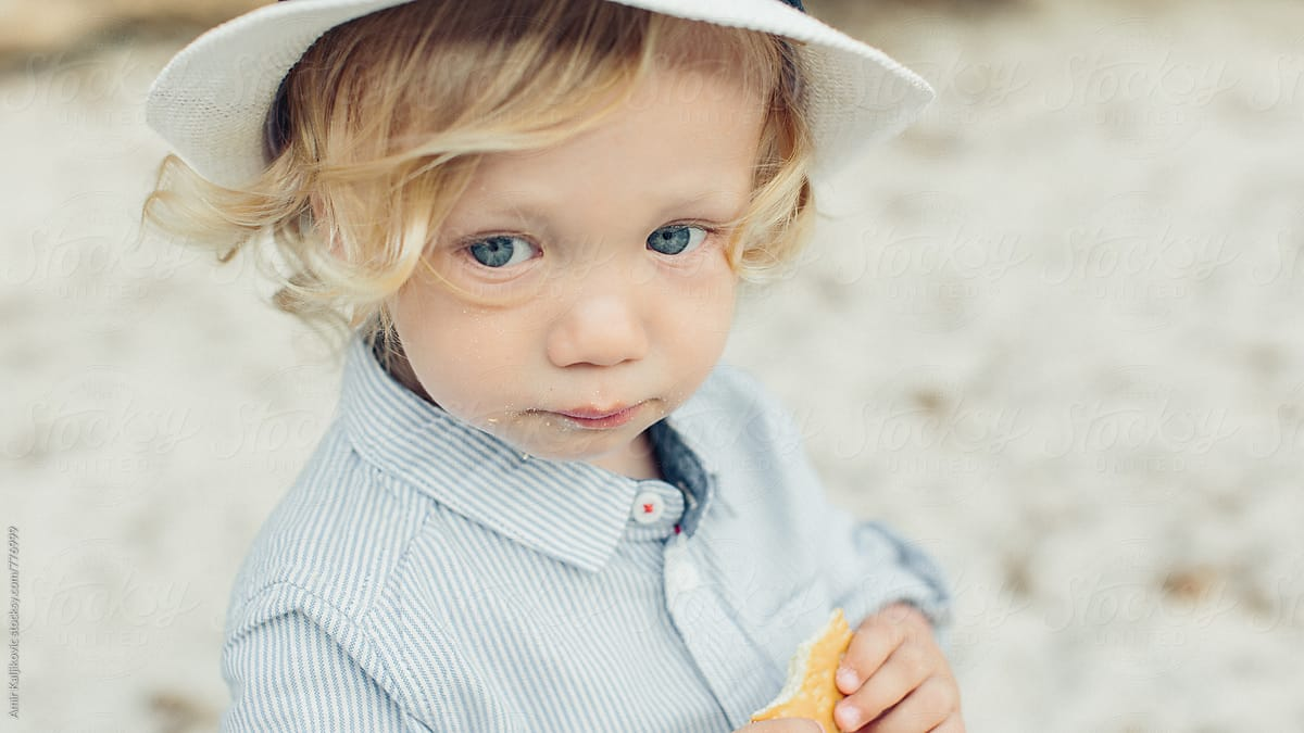cute little blond boy with a solemn expression | stocksy united