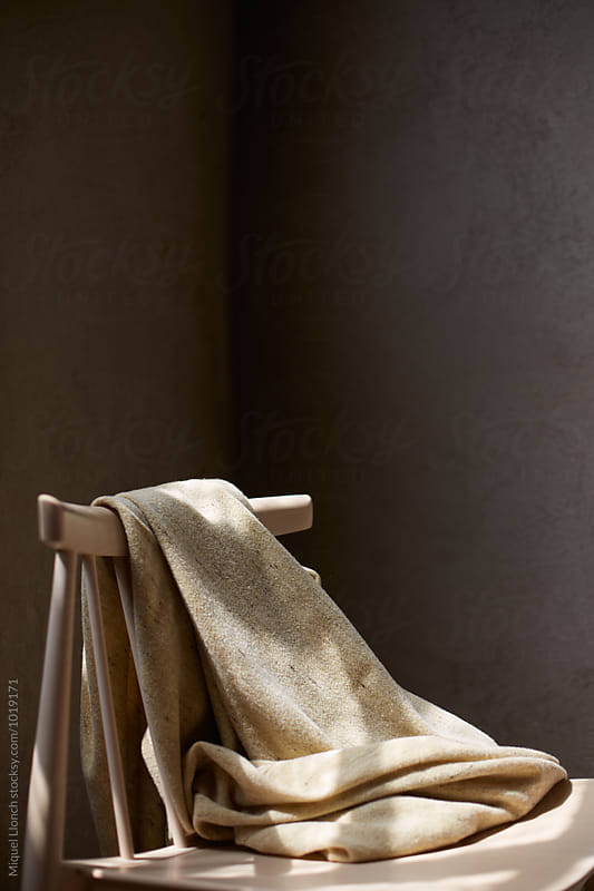 Wool blanket with wooden chair by Miquel Llonch for Stocksy United