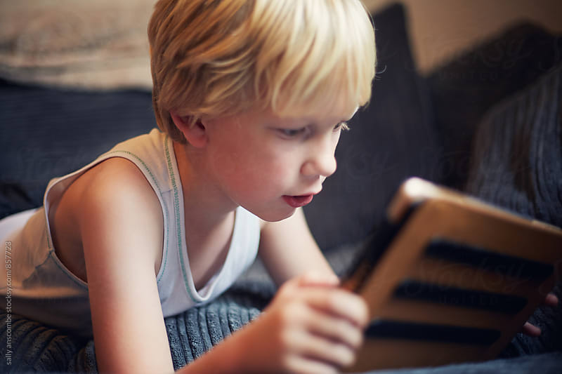Child using a digital tablet by sally anscombe for Stocksy United