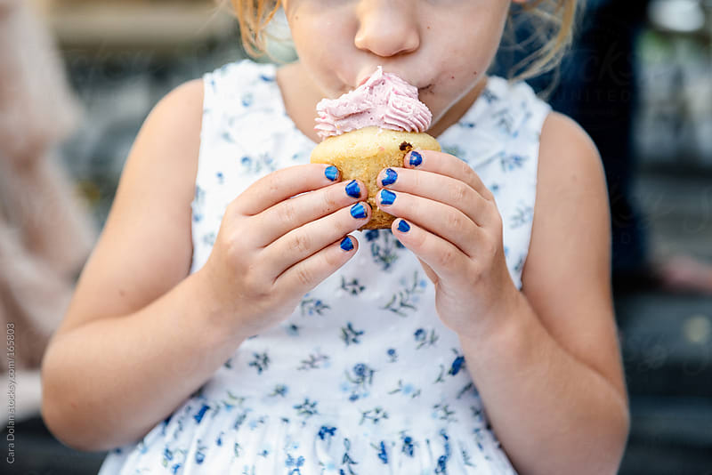 Little girl eats a cupcake at a party by Cara Dolan for Stocksy United