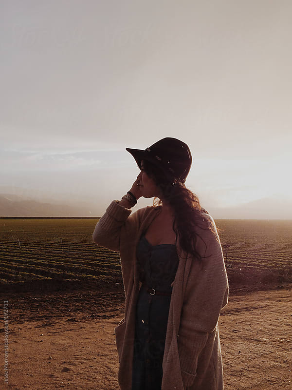 Young woman stands between sun and rain next to field by Jesse Morrow for Stocksy United