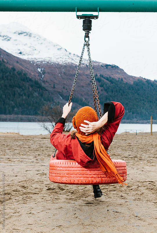 Portrait of a fashionable mischievous elderly woman on a swing set on the beach by Mihael Blikshteyn for Stocksy United