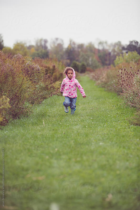 Portrait of a young girl in a pink hood running down a green grassy lane outside by anya brewley schultheiss for Stocksy United