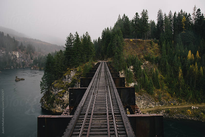 Train trestle over river on rainy day by Justin Mullet for Stocksy United