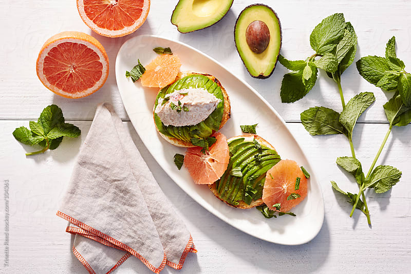 Gourmet breakfast bagel with tuna fish, avocado, grapefruit, and mint  by Trinette Reed for Stocksy United