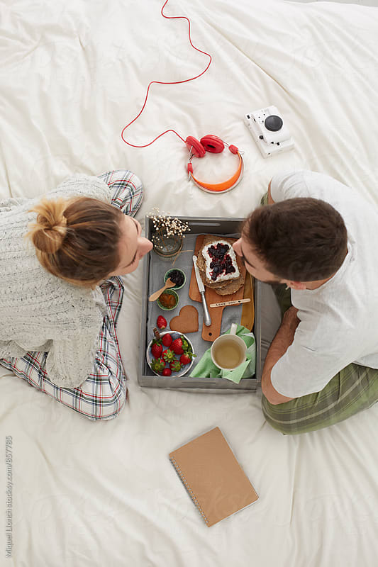 Young couple having a delicious breakfast on their bed by Miquel Llonch for Stocksy United