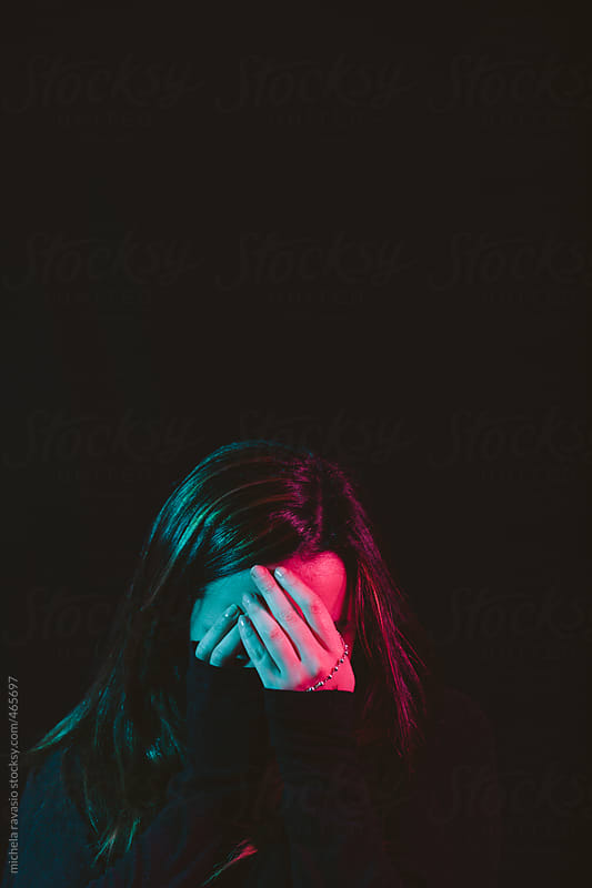 Young woman hiding her face with her hands by michela ravasio for Stocksy United
