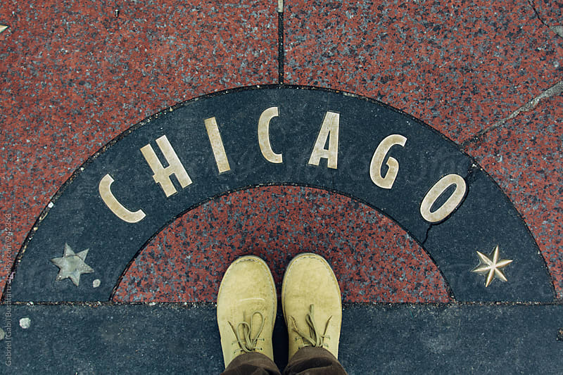 Pair of dessert boots on a Chicago sign in the sidewalk by Gabriel (Gabi) Bucataru for Stocksy United