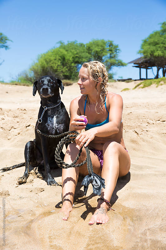 Blonde woman and her dog sitting on the beach by Curtis Kim for Stocksy United