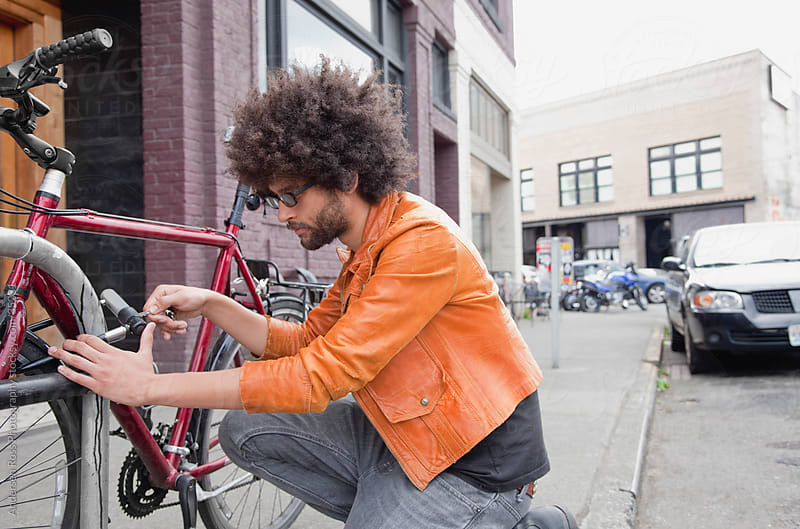 Young man locking his bike on sidewalk by Andersen Ross Photography for Stocksy United