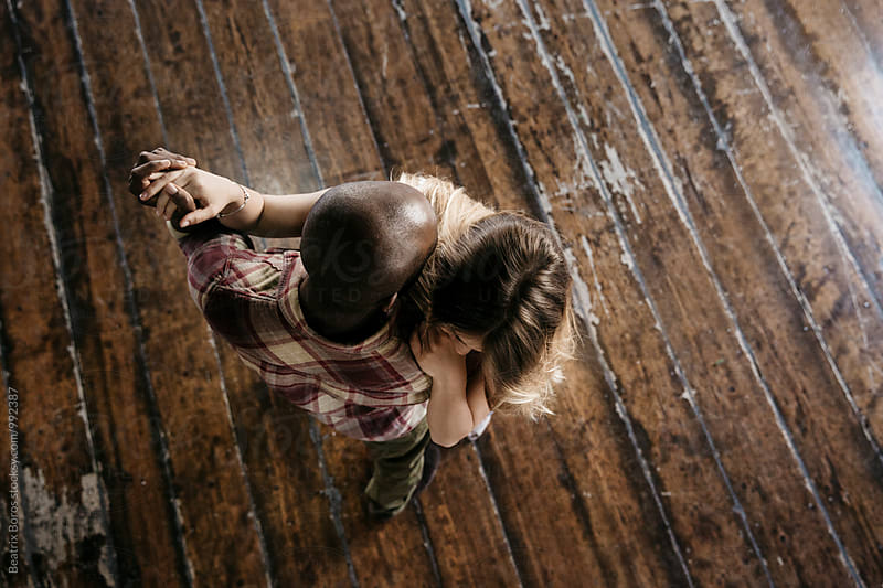 Mixed race couple dancing in a room, captured from above by Beatrix Boros for Stocksy United