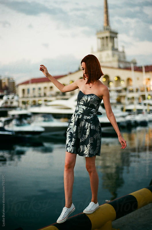 Woman balancing on a pipe at seaside by Lyuba Burakova for Stocksy United