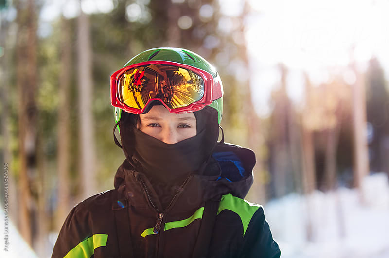 Boy with ski clothes, helmet and ski goggles ready to go skiing by Angela Lumsden for Stocksy United