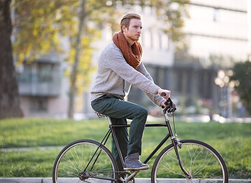 Red-Haired Man Riding a Bicycle by Lumina for Stocksy United