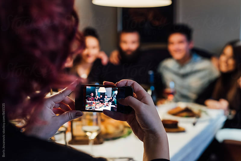 Group of friends having a photograph in the restaurant by Boris Jovanovic for Stocksy United