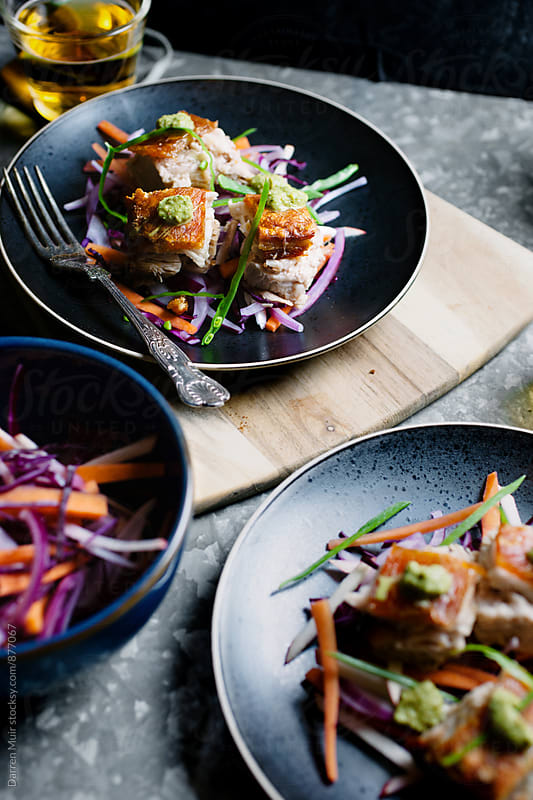 Pork belly and slaw on a black plate on a table. by Darren Muir for Stocksy United