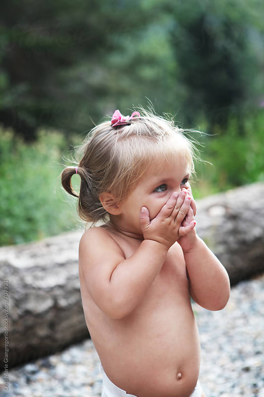 Toddler Girl Wearing No Shirt Outdoors Covering Mouth by Dina Giangregorio for Stocksy United