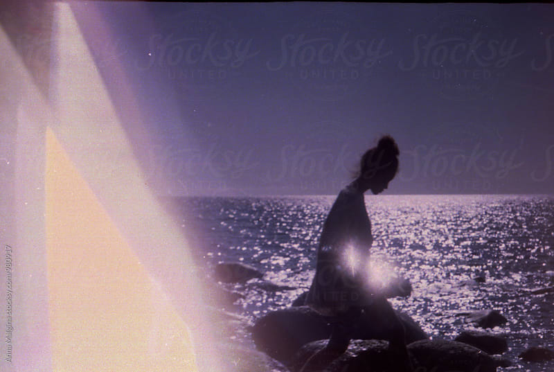A silhouette of young woman in front of a sea by Anna Malgina for Stocksy United