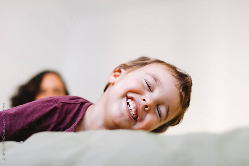 Happy boy laughing at home.  by BONNINSTUDIO for Stocksy United